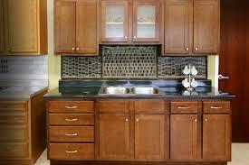 hickory wood red glass panel door kitchen and bath cabinets backsplash herringbone tile granite stone countertops sink faucet island lighting flooring