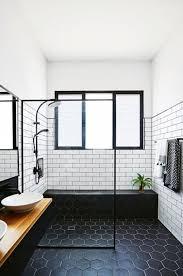 black framed window black hexagonal tile floor white subway tile wall wooden vanity above sinks potted plant
