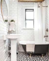 a soak black clawfoot bathtub on gilded legs in a small retro inspired bathroom