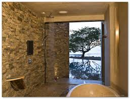 large shower space with natural stone tiles wall system a bathtub glass door feature ceiling showerhead