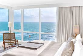 Modern white hotel corner unit bedroom with floor to ceiling windows and  close ocean view.