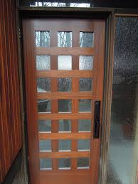 high single brown wooden frosted glass door with bars and black handler