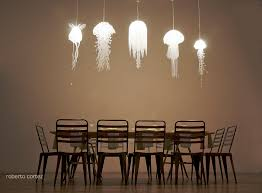the medusea collection of hanging lights by roxy rus above and below creates an incredible undersea world of jellyfish over the dining room table