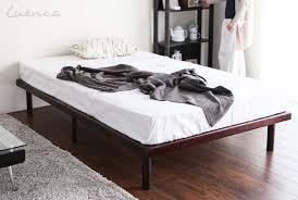 the cuenca japanese bed in dark brown with a white mattress over it