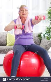 senior woman sitting on gym ball and exercise