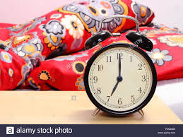Ringing Alarm Clock Set To 7am And Empty Bed In Bedroom In Background
