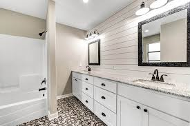 bathroom with white shiplap wall above dual vanity and spanish tile floor
