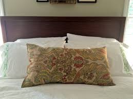 wooden headboard with bed pillows and pottery barn duvet covers
