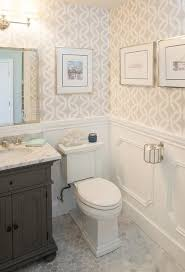 Chic powder room features top half of walls clad in beige geometric  wallpaper and lower walls