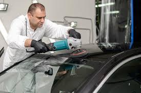 a professional auto glass repairman fixing a car