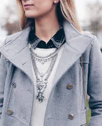 gray women s military coat with statement bib necklace over white crewneck sweater