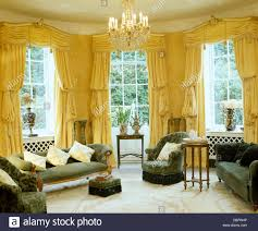 Silk Curtains For Living Room Yellow Swagged And Tailed Silk Curtains On Tall Windows In Yellow