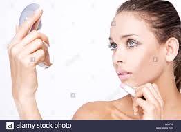 Makeup Beautiful woman applying lipstick holding small mirror