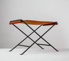 a foldable stool made of a black iron frame with a brown leather sling seat