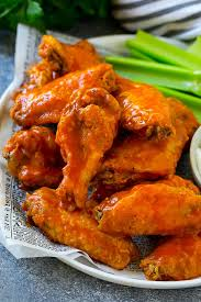 baked buffalo wings tossed in hot sauce served with celery sticks