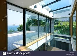 large sliding glass doors. Large Sliding Glass Doors Open. Floor To Ceiling Panels. A Low Profile Building In Seaside Location. View Out Sea
