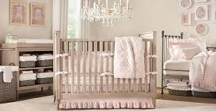 simple beige baby crib with soft pink bedding in white wall paint