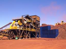 Shipping containers stacked to form a semi-permanent wall at an iron ore  mine in Western Australia