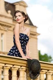 エレガントな髪型赤い口紅ショート ドレス手に帽子と古代の宮殿の