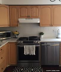 wood kitchen cabinets with white tile backsplash