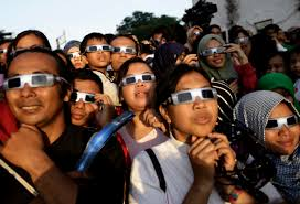 In this March 9 2016 file photo people wearing protective glasses look up  at the sun to watch a solar eclipse in Jakarta Indonesia