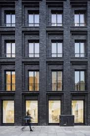 Gridded brick facade. This looks so good! Painting brick buildings black is  such a