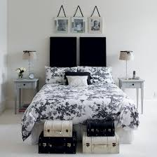 White guest bedroom with double bed with raised headboard, floral bedding  and storage boxes |