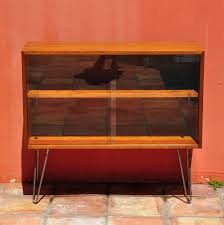 furniture brown stained wood two shelf media cabinet with sliding glass door having metal leg mid century modern media console decor ideas home interior