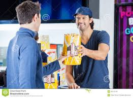 worker selling popcorn to man at concession stand stock photo worker selling popcorn to man at concession stand