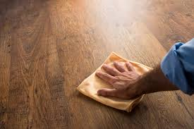 male hand cleaning and rubbing an hardwood floor with a microfiber cloth