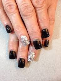 Acrylic nails finished with black gel polish with full silver ...