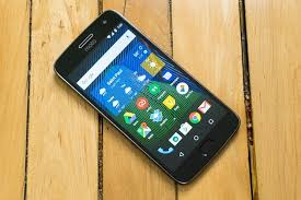 moto android phone. a moto g5 plus android phone laying on wood surface. m