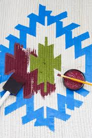 using a foam brush to paint a kilim pattern onto a rug