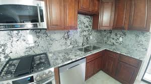 light color granite countertops kitchen countertop with backsplash and dark cabinets close up