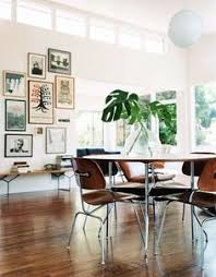beautiful modern dining room with a gallery wall and eames designed furniture