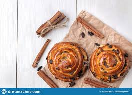 Tasty Buns With Raisins And Cinnamon On A White Wooden Background