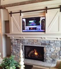 love this barn doors covering tv over the mantel except that i would really miss my mantel so maybe elsewhere in the room shutters or barn door