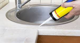 Plumber Putting A Silicone Sealant To Installing A Kitchen Sink - Installing a kitchen sink