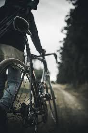 Road biking wallpapers wallpaper cave. Hd Wallpaper Selective Focus Photography Of Person Holding Gray Road Bike On Road Wallpaper Flare