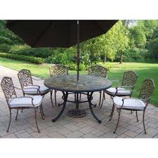 9 piece metal outdoor dining set with tan cushions and brown umbrella