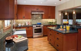 oak mission cabinets feature black iron hardware in remodeled kitchen featuring bi level peninsula