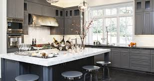 dark grey kitchen cabinets with white countertops island and round chair with big window and hardwood flooring