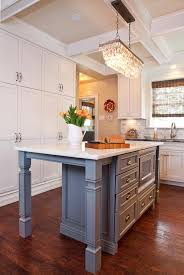 a pottery barn clarissa crystal drop extra long rectangular chandelier stands over a gray kitchen island with turned legs fitted with a microwave oven
