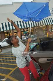 Brandy Randle battles the wind and rain as she loads groceries at ...