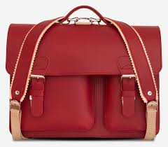 front view of red leather satchel backpack with 2 gussets and asymmetric front pockets for women
