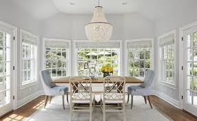blue and grey dining room features a white flower chandelier illuminating a reclaimed wood trestle dining table lined with light taupe lattice back dining