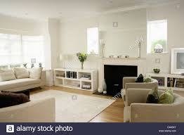 modern white living room furniture. Low White Shelf Unit Beside Fireplace In Modern Living Room With Tub Chairs And Wooden Floor Rug Furniture I