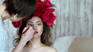 makeup artist stylist works with model make up of a young in a beauty salon make up artist who uses make up on the face of the model