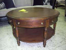 rustic round wood coffee table with storage drawers and ample shelf underneath a gallery of