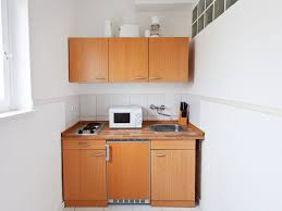 countertop microwave in white tiny kitchen appliances over small granite countertop under goldenrod kitchen cabinet also white tile backsplash in minimalist